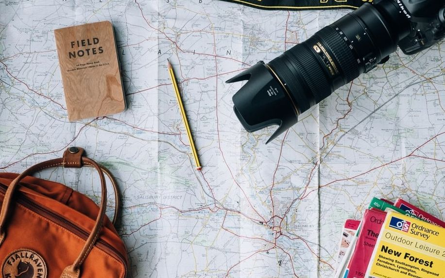 travel bag and camera lying on an open map