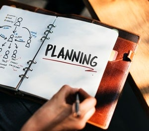 Hand and Notebook image for Benefits of a Personal Development Plan
