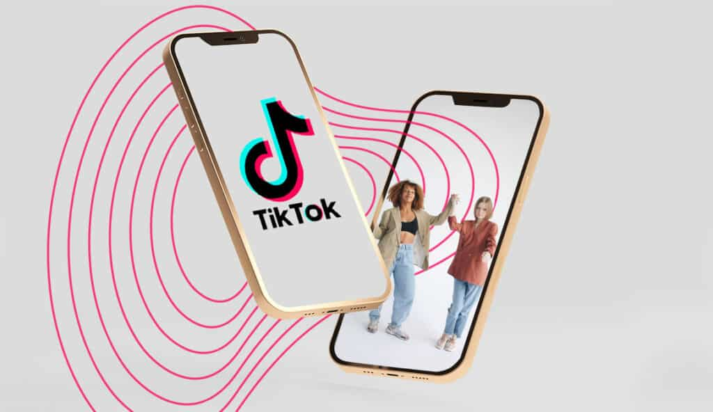 Grey background with two phones hovering - one with the TikTok logo and another with two women dancing