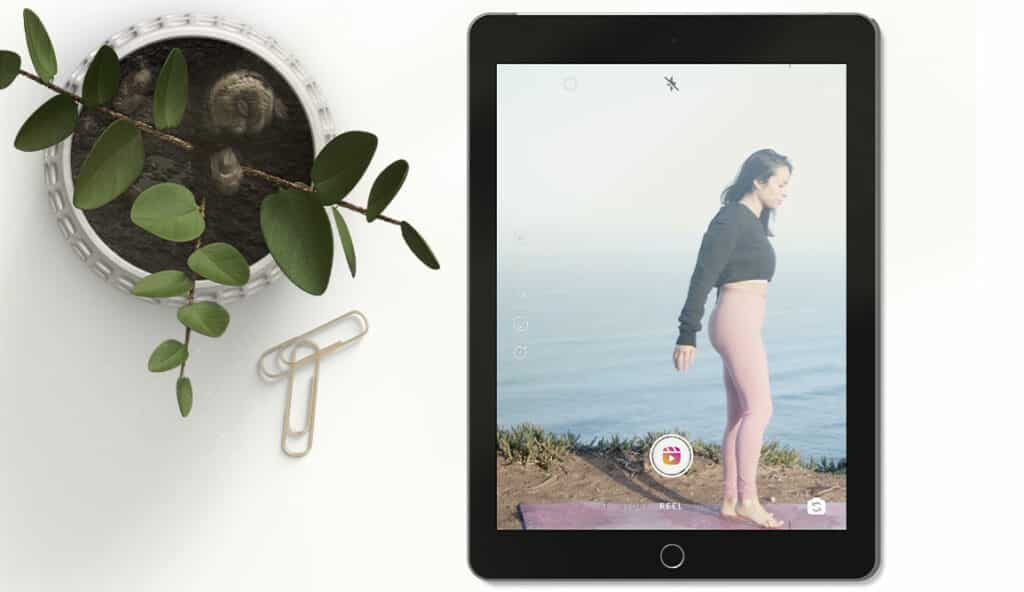 Flat lay of tablet showcasing an Instagram Reel of a woman by the sea. To the left-hand side, a plant and paperclips on a white background.
