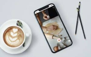 A smart phone on a white coffe table showing loading an Instagram reel