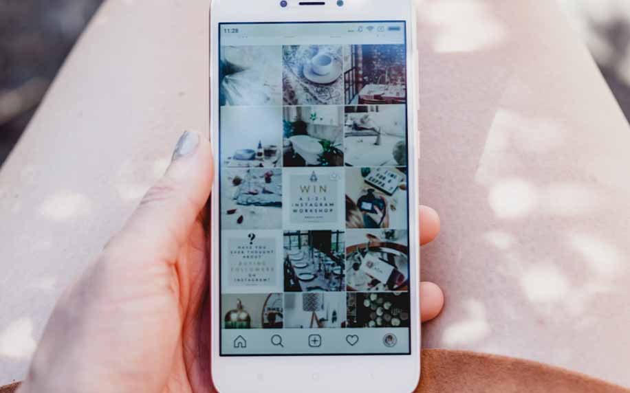 a marketer holding a phone with an Instagram grid open, browsing it