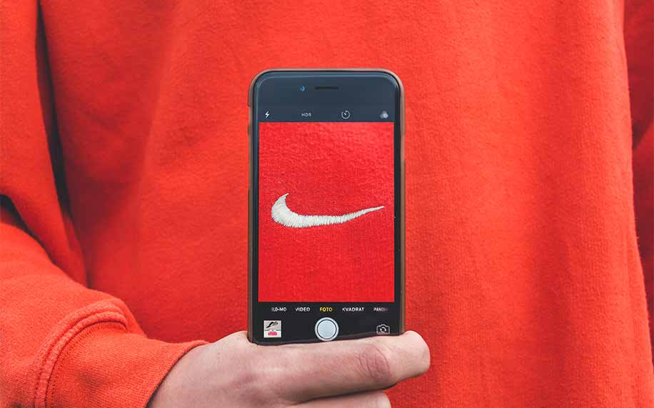 man holding a phone taking a picture of the nike logo on his jumper showing brand awareness