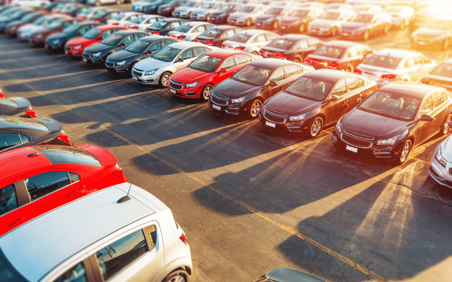 car dealership, row of cars outside in car park with sun shining in top right hand corner
