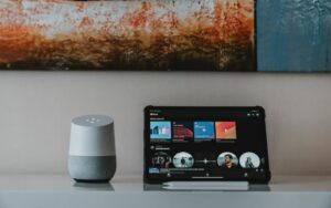 A photo of a Google Home speaker and tablet on a desk.