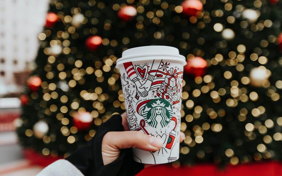 A woman holding a christmas-themed Starbucks cup in front of a lit up Christmas tree