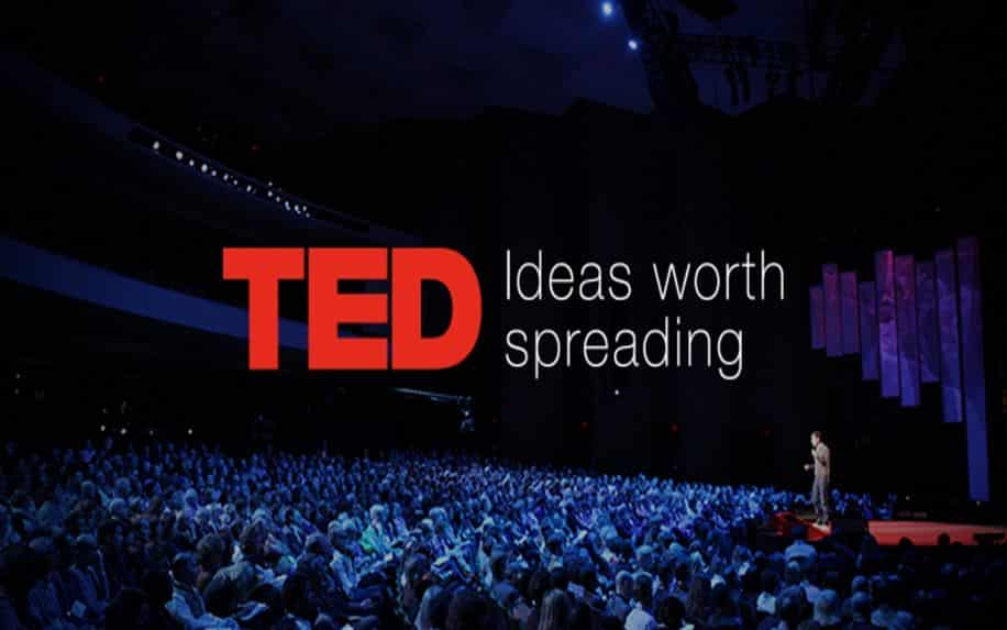 A photo of a man giving a TED Talk to a large audience. The words TED: Ideas worth spreading are written over top of the image