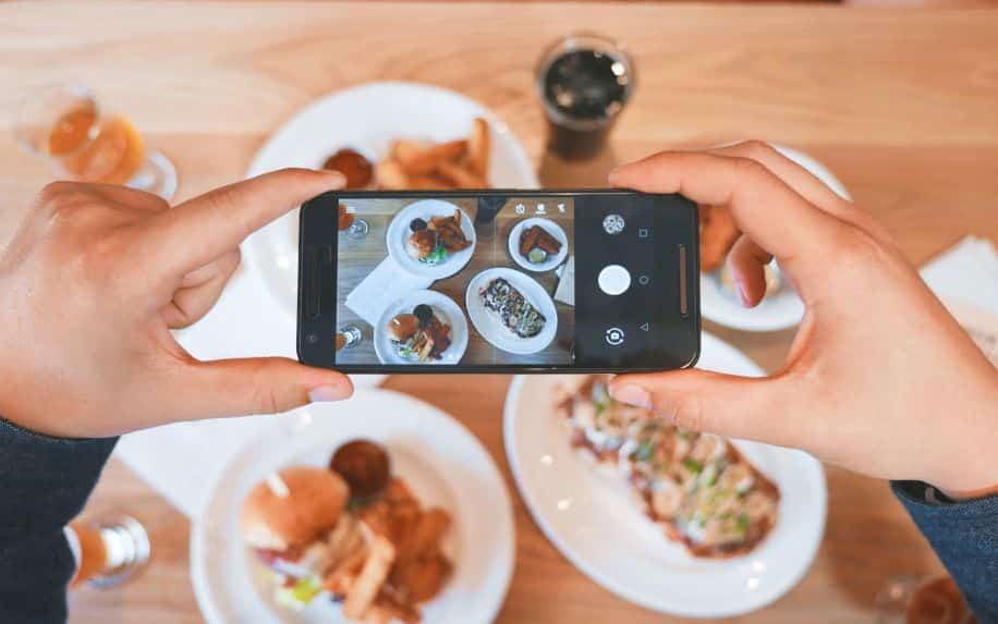 A person taking a photo of their food on an iPhone