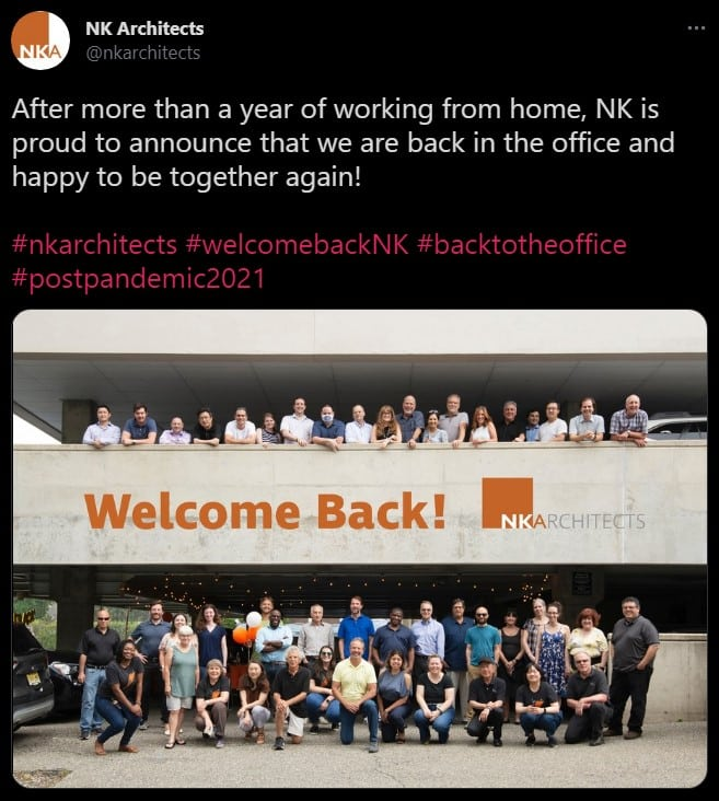 A Twitter post from NK Architects celebrating being back in the office. A photo of their staff in front of a parking garage is included.