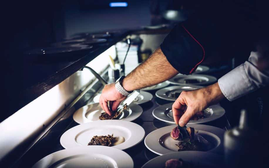 Two chefs plating in the kitchen