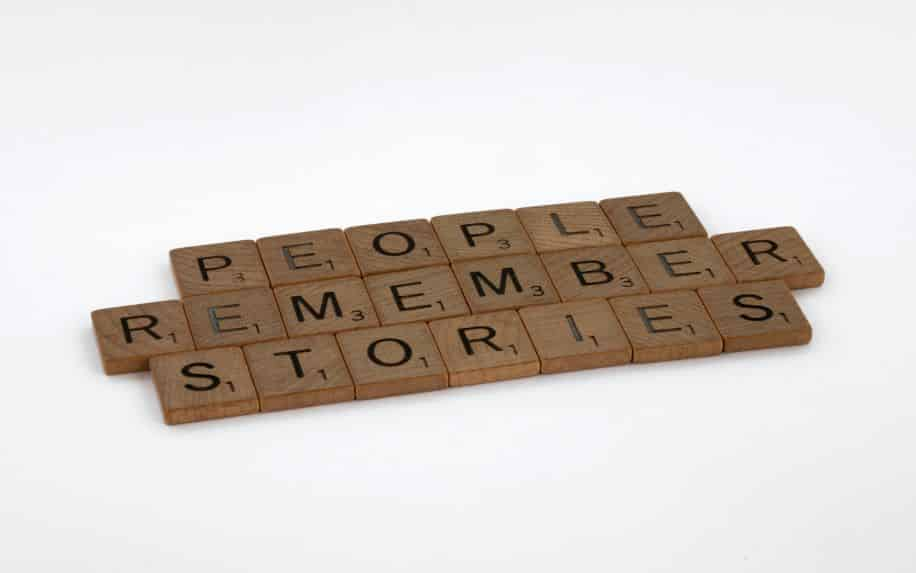 """Scrabble game pieces spelling out the phrase """"people remember stories"""""""