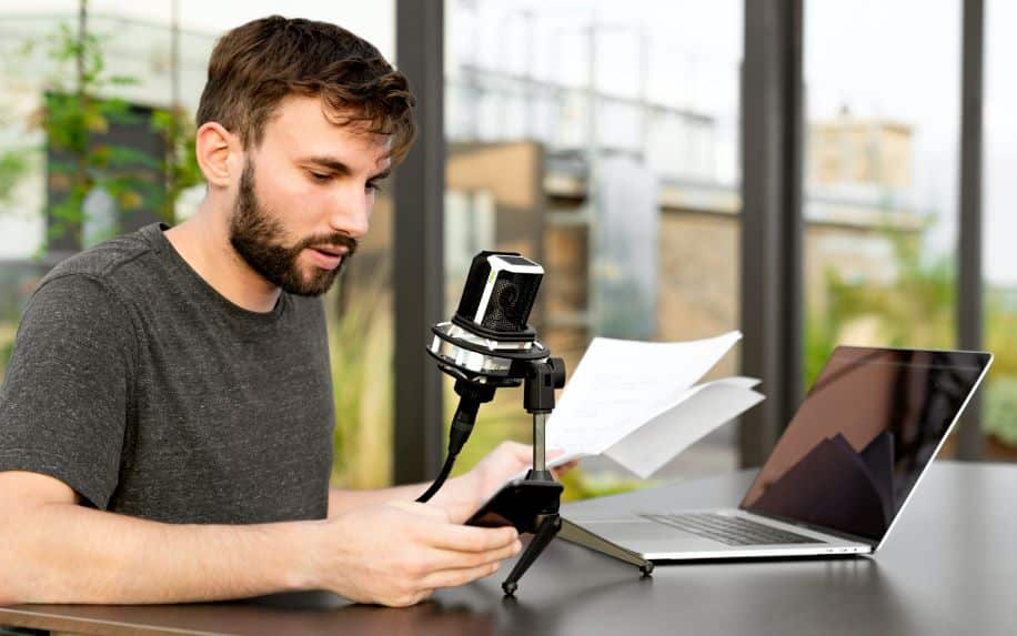 A man reading a script off of his phone into a microphone. The mic is connected to his Macbook.